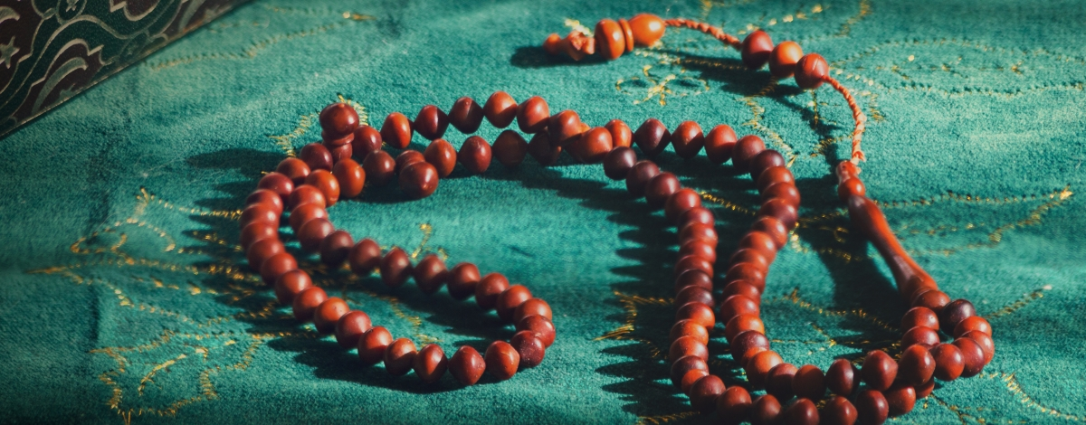 Prayer beads in front of a hard cover book on a green background.
