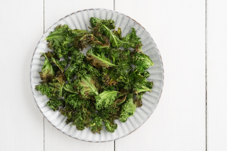 Kale chips with sea salt on a white plate