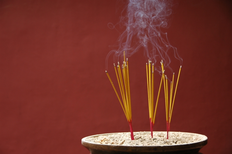 Sticks of burning incense on dark red background