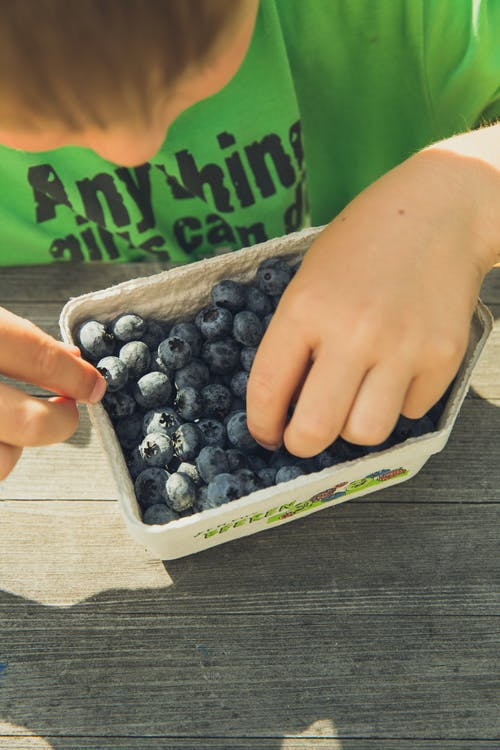 young boy with blueberries