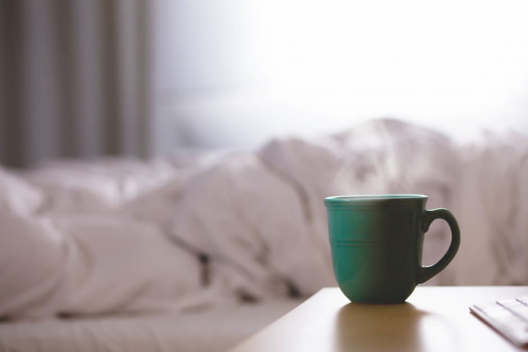steaming cup of coffee in bedroom