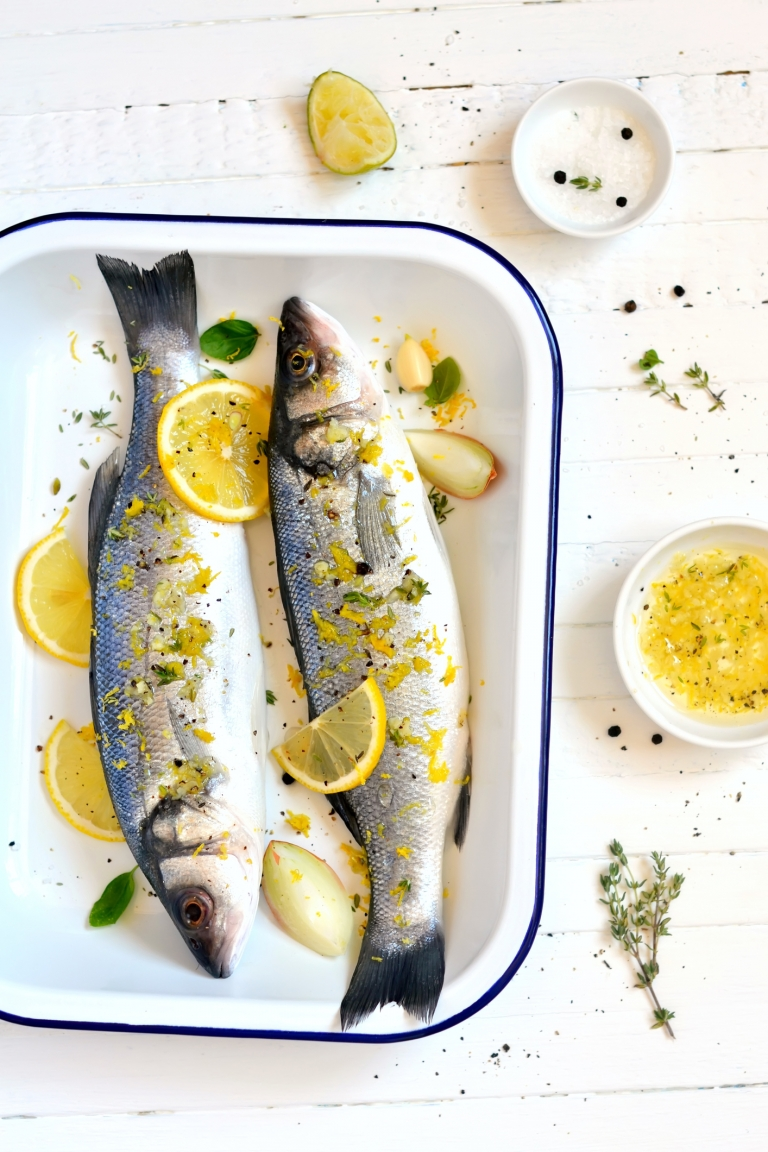 sea bass with lemon and thyme on a light background